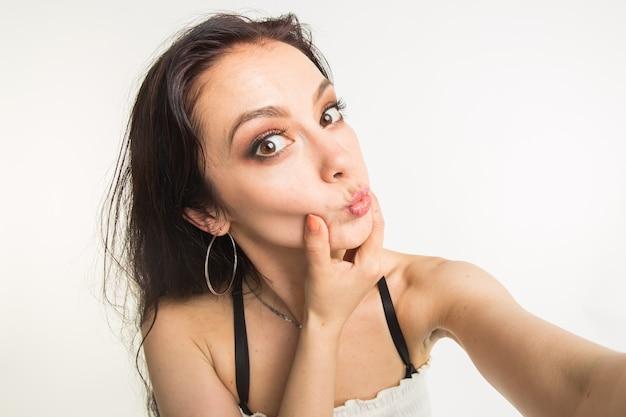 사진과 사람들 개념-재미 있은 얼굴로 셀카 사진을 만드는 아름다운 여자를 닫습니다