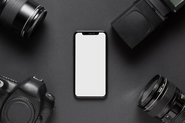 Photography concept with camera accesories and smartphone in the middle