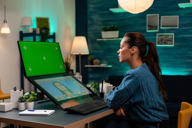 디스플레이에 녹색 화면이 있는 사진 수정 작업을 하는 사진 디자이너. 편집 스튜디오의 그래픽 소프트웨어에서 모형 템플릿과 격리된 크로마 키를 사용하는 전문 여성