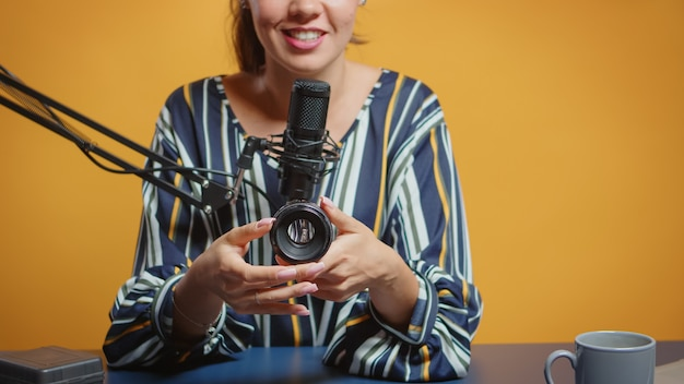 Photography expert talking about camera lens in her weekly podcast for subscribers. content creator new media star influencer on social media talking video photo equipment for online internet web show
