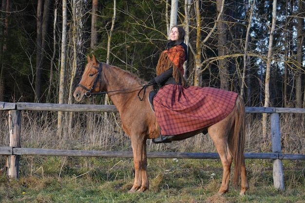 A photography of a girl in national dress and riding a horse