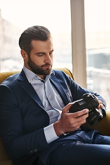 Photography is a great hobby closeup portrait of young bearded and well dressed businessman who