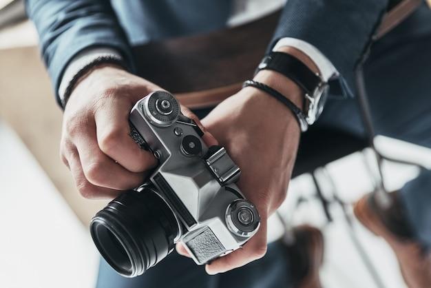 写真は彼の情熱です。椅子に座っている間写真カメラを保持している若い男のクローズアップ