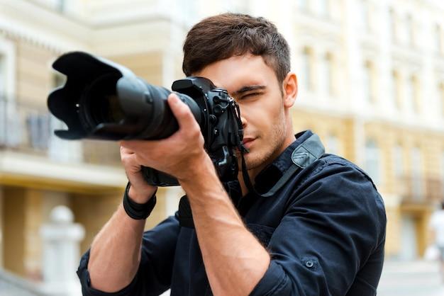 写真は私の情熱です。屋外に立って何かを撮影する自信を持って若い男