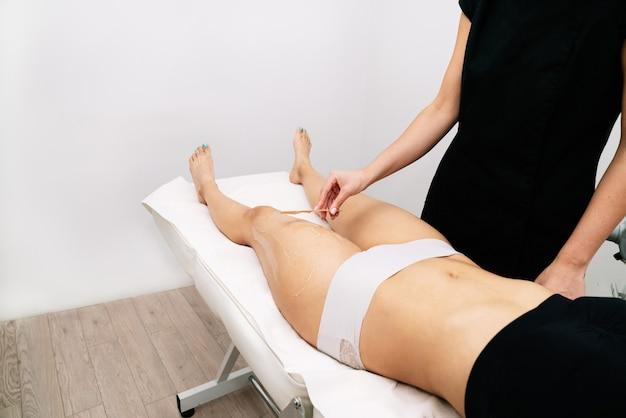 Фотография косметолога, делающего восковую депиляцию женщине на бедре в клинике, на белом фоне