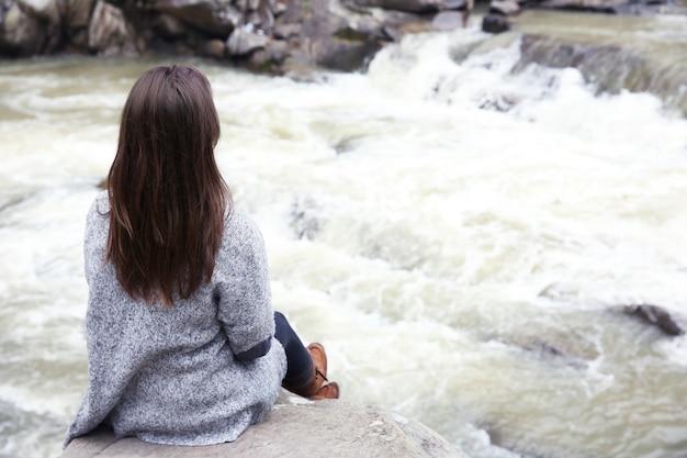 岩の上の美しい滝の近くの女性の写真