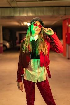 Фотография с красными и зелеными неонами на стоянке. портрет молодой довольно белокурой кавказской женщины в красном костюме и солнцезащитных очках