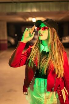Фотография с красными и зелеными неонами на стоянке. портрет молодой довольно белокурой кавказской женщины в красном костюме, солнцезащитных очках и черной кепке
