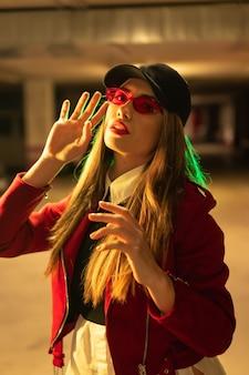 Фотография с красными и зелеными неонами на стоянке. молодая красивая белокурая кавказская женщина в красном костюме, солнцезащитных очках и черной кепке
