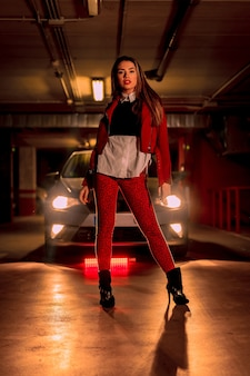 Photography with red neon in front of a car in a parking lot. portrait of a pretty young blond caucasian woman