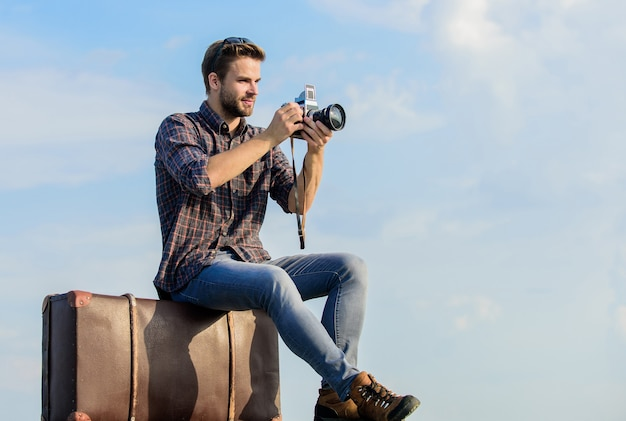Photojournalist concept. travel with luggage. travel blogger. shooting vlog. vacation time. travel blog. man sit on suitcase. handsome guy traveler retro camera. guy outdoors with vintage suitcase.