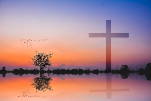 Photomontage of cross against silhouette of mountain and lake view at sunset