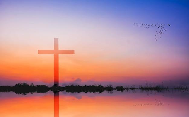 Фотомонтаж креста против силуэта горы и озера на закате