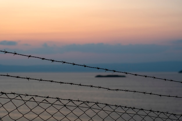 사진: 철조망, 바다, 구름, 일몰.