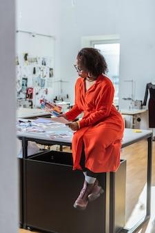 더미에서 사진. 영감을 찾고 잡지에서 사진을 관찰 호기심 곱슬 검게 그을린 여자