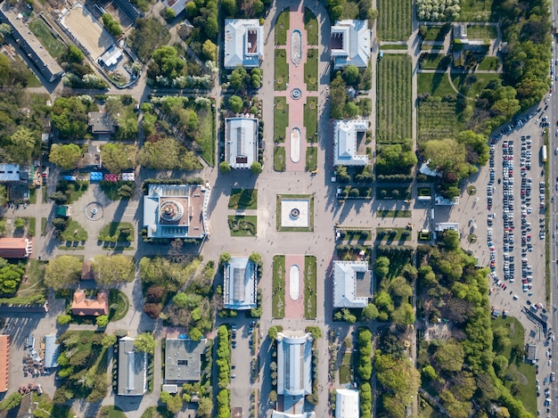 우크라이나 키예프에있는 자동차 주차장이있는 국립 전시 센터의 대칭 광장과 건물을 볼 수있는 드론의 사진.