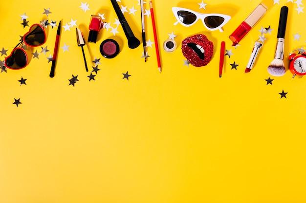 黄色い壁にスタイリッシュな女性用メガネ、唇の形をしたブローチ、化粧品の写真がクリエイティブに配置されています