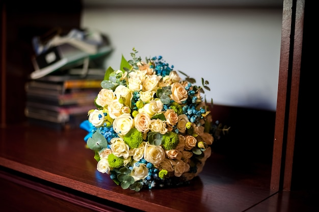 Фотографии свадебного букета в бело-голубых тонах лежат на полке.
