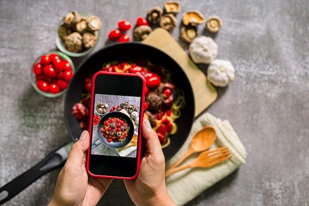 Фото поиск по imсфотографируйте спагетти на мобильный телефонвид сверху на женщину, делающую фото