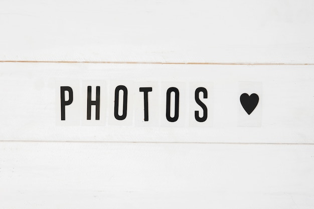 Photos text and black heart shape on white wooden background