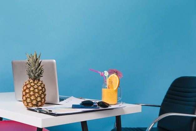 Photos of workplace during holidays. pineapple, orange cocktail, glasses, graphics, laptop are on table.