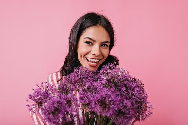 写真。彼女の手に肖像画のポーズをとって大きなライラックの花束を持つ少女。