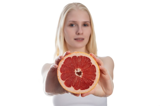 Photoset of attractive girl holding a cut piece of sicilian orange on white background