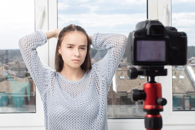 집에서 촬영. 카메라 앞에서 포즈를 취하는 소녀, 사진을 찍는다