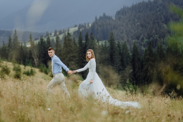 Photoshoot of the bride and groom in the mountains. boho style wedding photo.