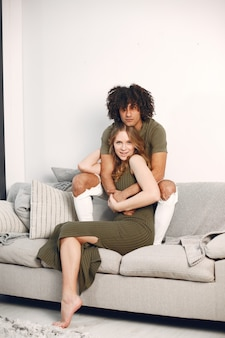 Servizio fotografico felice giovane coppia a casa sul divano. abbracciare, baciare.