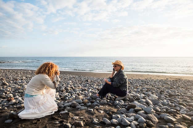 Photoshooting with two females. one photographer and a mature woman speaking at the phone to represent a nice lifestyle on the beach. stock and advertising concept work