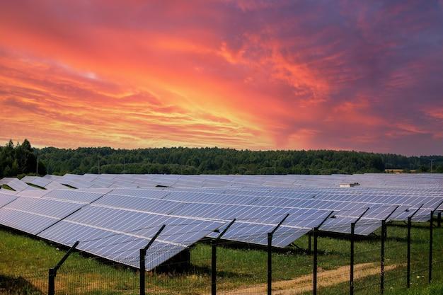 劇的な夕焼け空の背景に太陽光発電モジュール太陽光発電所。クリーンな代替電力エネルギーの概念。