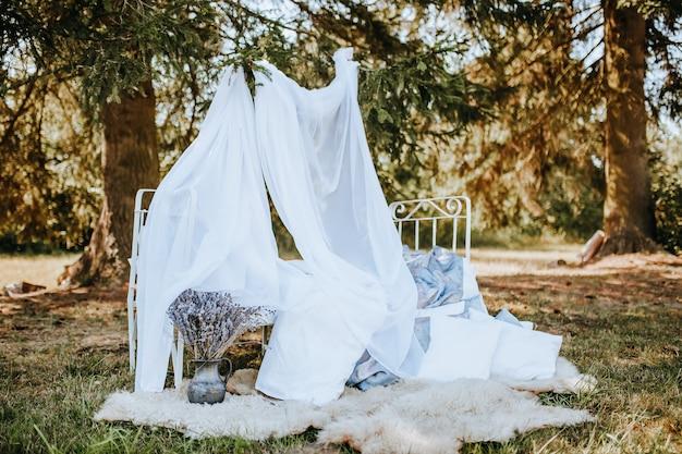 自然の森のフォトゾーン天蓋付きベッド。生地が風になびく。花嫁の写真のための場所。撮影会