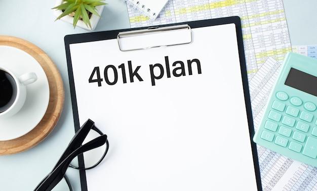 펜, 계산기, 안경 및 차트 보고서가있는 종이 클립 보드에 작성된 문구 401k 계획. 금융 및 비즈니스 개념.