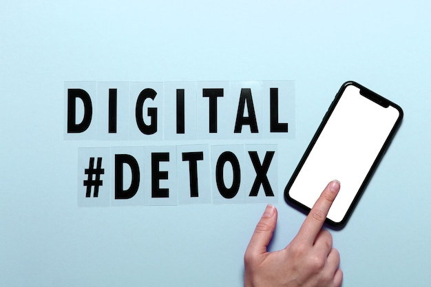 Phrase digital detox and female hand with smarthone. blue background,hashtag, top view.