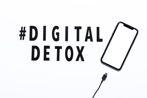 Phrase digital detox and smarthone with unplugging charge cable. white background,hashtag, top view.