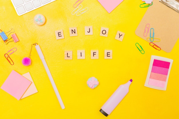 Phrase enjoy life and various stationary and keyboard on yellow background, top view