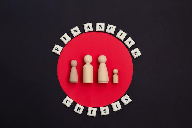 Phrase financial crisis and wooden family figures.