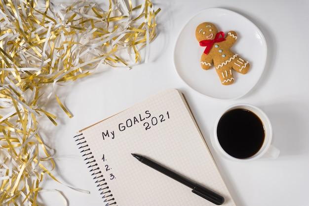 Фраза «мои цели на 2021 год» в блокноте, ручка. кружка кофе, пряничный человечек и мишура. вид сверху.