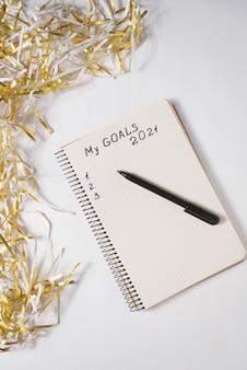 Фраза «мои цели на 2021 год» в блокноте, ручка. мишура на белом фоне.