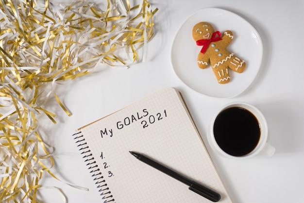 Phrase my goals 2021 in a notebook, pen. mug of coffee, gingerbread man and tinsel. top view.