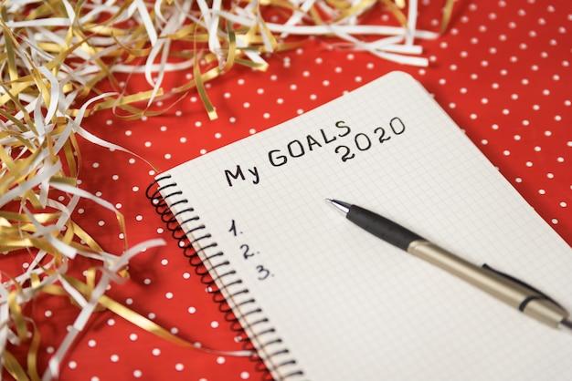 Phrase my goals in a notebook, black pen.