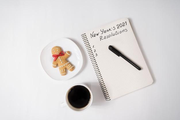 Фраза «новогодние резолюции 2021» в блокноте и ручке. пряничный человечек и чашка кофе.