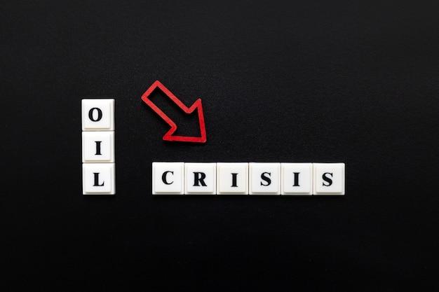 Фраза нефть кризис из пластиковых печатных букв с красной падающей стрелкой