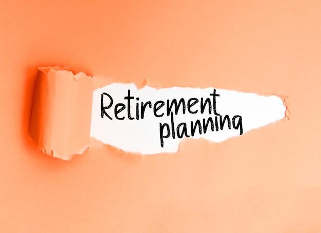 Фраза пенсионного планирования на английском языке, написанная на порванной бумаге.
