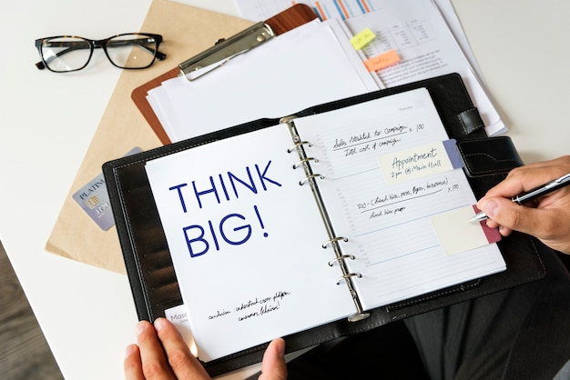 Phrase think big written on a notebook