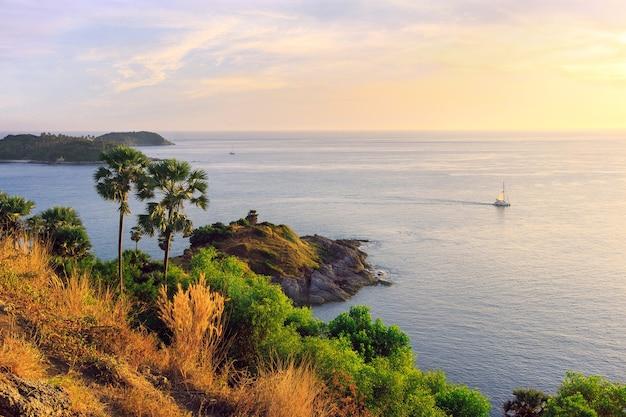 Мыс промтхеп на закате, живописный вид на андаманское море на острове пхукет, таиланд. морской пейзаж со скалами и зелеными пальмами на фоне оранжевого неба и одинокий парусник, плывущий вдаль.