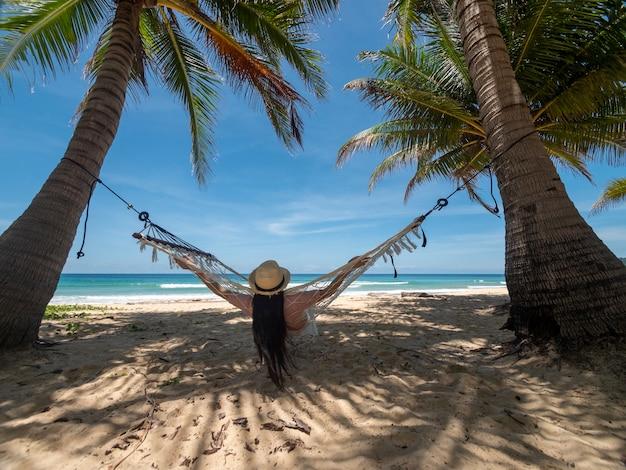 태국 푸켓. 해질녘 해변에서 해먹에서 휴식을 취하는 아시아 젊은 여성. 해먹에서 스윙하는 젊은 매력적인 여성. 휴가 휴가 여름