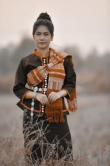 Phutaiのアジアの女性が牧草地で衣装します。