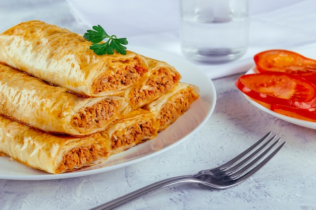 Phyllo pasta rolls with tuna ready to eat on a white table